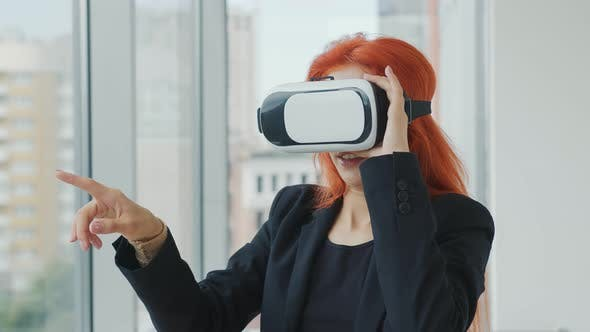 Thumbnail for Young Pretty Red-haired Woman Wearing VR Glasses. The Woman Is in Virtual Reality Thanks To VR