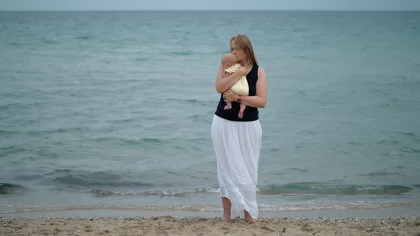 Thumbnail for Mother Cuddling Baby Scene at the Beach Against the Sea