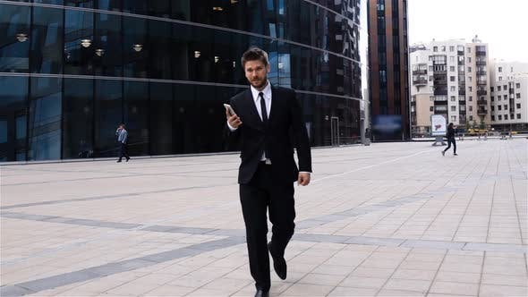 Thumbnail for Young Businessman Walking, Using Phone in Business District