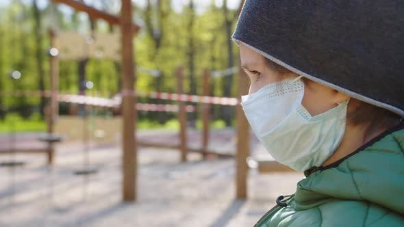 Thumbnail for a Boy Wearing a Protective Mask Near a Closed Playground
