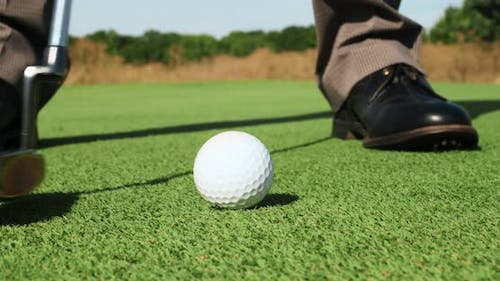 Close Up of Professional Male Player Hitting Ball with Golf Club Practicing Playing Golf Outdoors