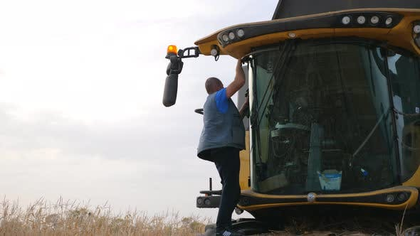 Thumbnail for Unrecognizable Farmer Cleaning His Combine After Harvesting