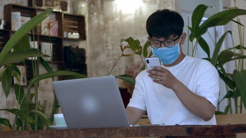 Man with Glasses. Asian-looking Teenager in Protective Mask, Student Working on Phone From Cafe and