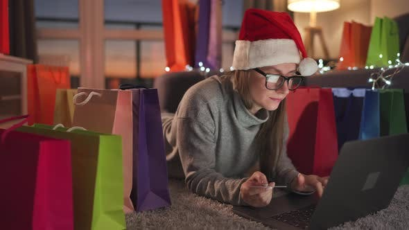 Happy Woman with Glasses Wearing a Santa Claus Hat Is Lying on the Carpet and Makes an Online