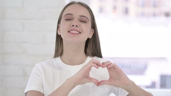 Thumbnail for Portrait of Attractive Young Woman Making Heart Shape
