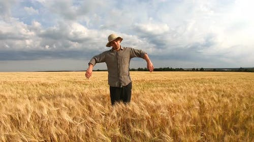 Young Agronomist Standing at Ripe Barley Meadow and Looking Like a Scarecrow