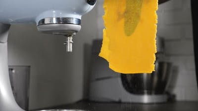 Chef Making Homemade Pasta with Turmeric and Spinage Leaves Inside on Professional Equipment Pasta