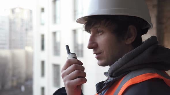 Thumbnail for A Builder From a High-Rise Building Coordinates Work Using a Walkie-Talkie