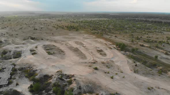 Flying Over an Empty Sandy Playground for Motocross Training