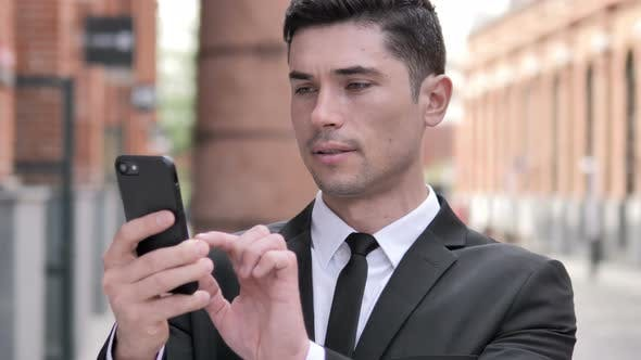 Thumbnail for Outdoor Businessman Celebrating Success on Smartphone