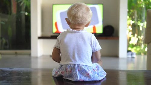 Back View of a Little Girl Sitting on the Floor Watching the Tv