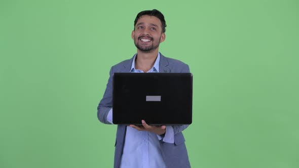 Thumbnail for Happy Young Bearded Persian Businessman Thinking While Using Laptop