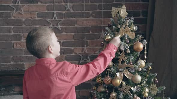 Thumbnail for Blond Kid Rearranges Bow Decorations on Christmas Tree