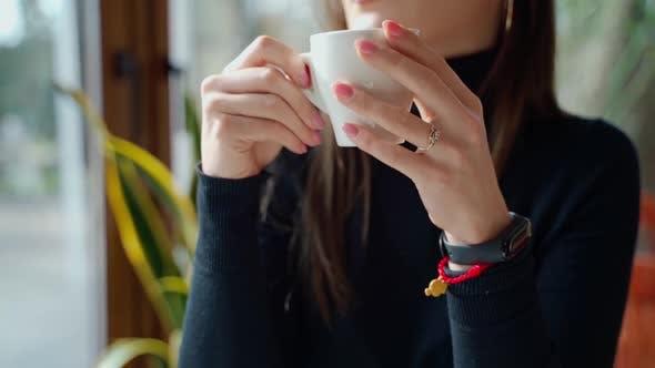 Beautiful girl drinking coffee in a cafe
