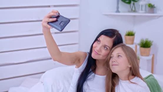 Family Values, eine schwangere Mutter mit ihrer Tochter nimmt ein Selfie am Telefon. Foto für Memory, Mama