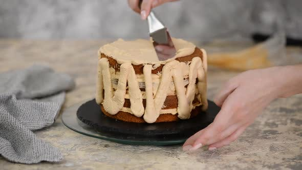 Cover Image for Girl Making a Cake in a Bakery. Baker Squeezes Cream Onto a Cake Layer.