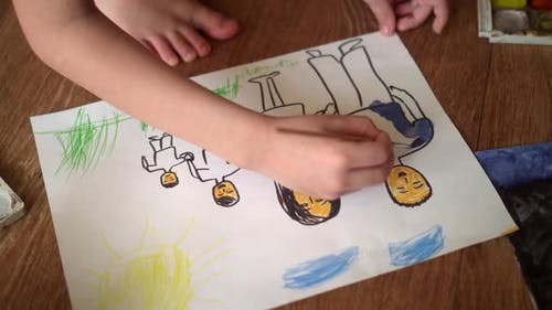 A Child Paints a Drawing on the Floor with Watercolors