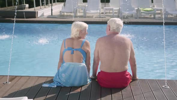 Thumbnail for Back View of Happy Mature Couple Sitting on the Edge of the Pool