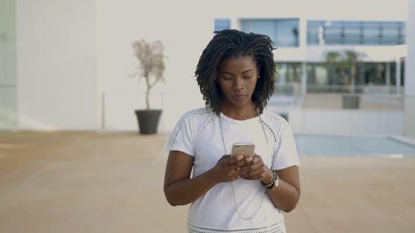 Thumbnail for Lächelnde Frau mit modernen Smartphone beim Bummeln auf der Straße