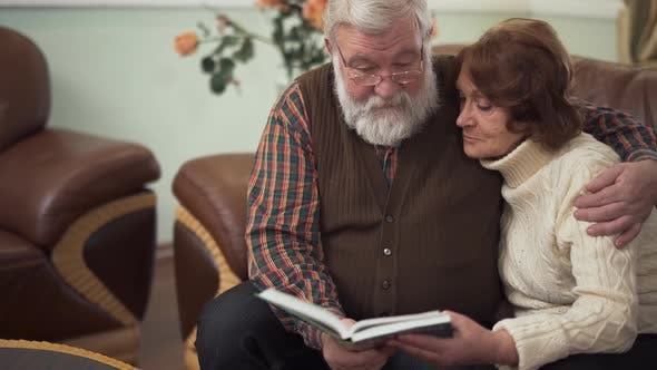 Thumbnail for Elderly Couple Look Into a Big Book or Album