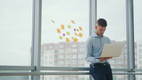 Thumbnail for Young Successful Businessman in the Office By the Window Working with a Laptop. The Man Solves