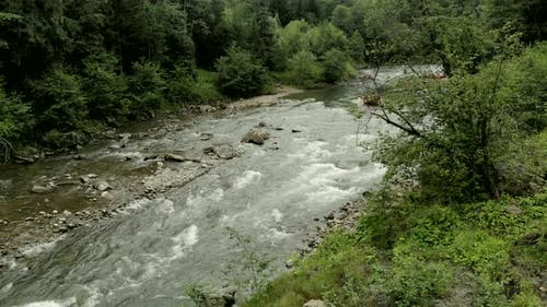 People Kayaking on Rapid Mountain River