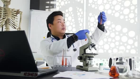 Thumbnail for Asian Doctor in white Gown and Blue Gloves Comparing Filling of Two Test Tubes