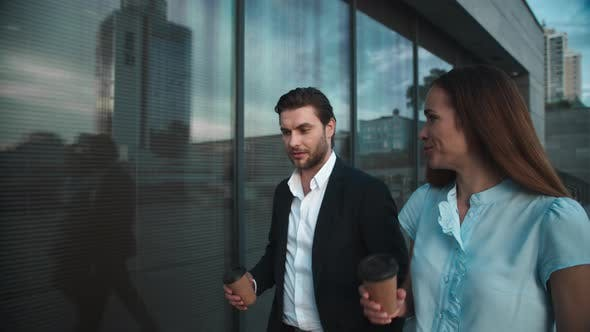 Thumbnail for Businessman and Businesswoman Walking in City, Colleagues Drinking Coffee