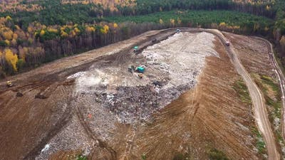 Landfill. A Huge Pile of Garbage Surrounded By Forest. Garbage Trucks Carry Garbage To a Landfill.