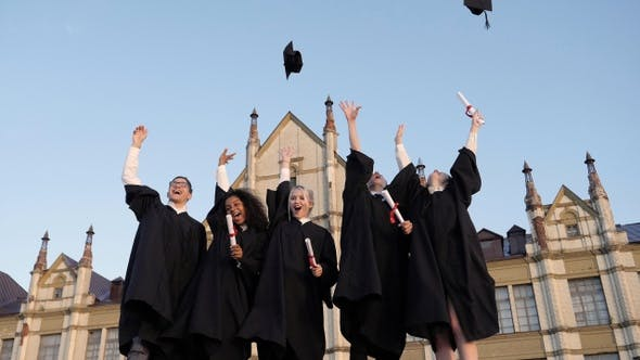 Thumbnail for Graduation Caps Are Tossed Into The Air By A Happy Group