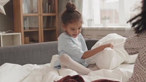 Kids Having Pillow Fight on Bed