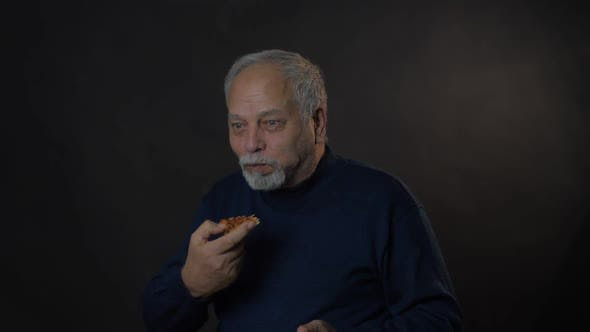 Thumbnail for Delighted Man in Blue Pullover Eats Pizza and Looks Straight