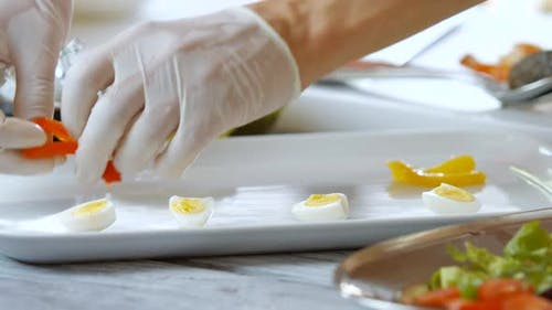Hands Put Eggs on Plate.