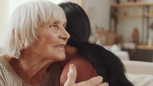 Senior Grandmother Hugging Adult Granddaughter at Home