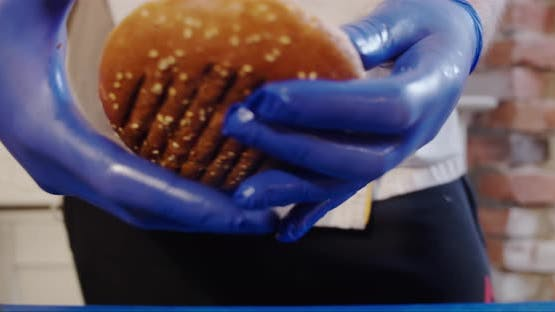 Close Up. The Cook Hands Placing Top Bun on a Burger. . Slow Motion