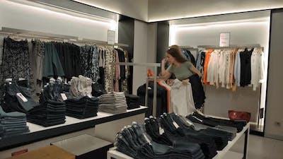 Female Friends Choosing Clothes in Shop