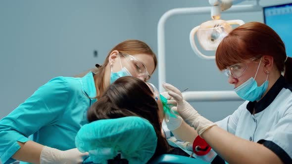 Stomatologist and a nurse during tooth treatment