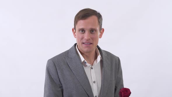 Cover Image for Portrait of Genuine Self-confident Man in Suit Extends a Hand Forward Holding Red Rose Isolated