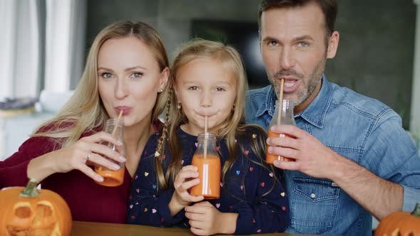 Thumbnail for Cheerful family drinking pumpkin smoothie