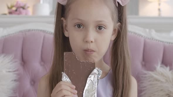 Thumbnail for Close-up of Happy Little Girl Chewing Chocolate at Home. Satisfied Face of Pretty Brunette Caucasian