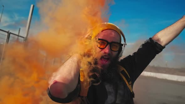 Thumbnail for Portrait of a Hipster in Yellow Glasses. Dancing Street Dance with Orange Smoke. Slow Motion