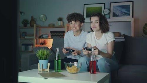 Beautiful Girls Playing Video Game at Home at Night Having Fun Sitting on Sofa