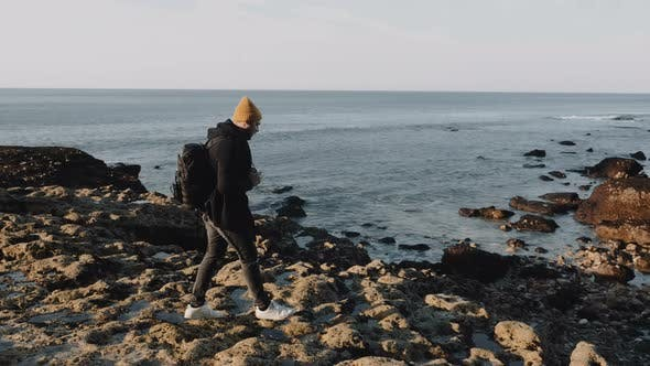 Thumbnail for Happy Male Photographer Stepping on Rocky Beach, Taking Pictures of Stunning Sunny Normandy Shore