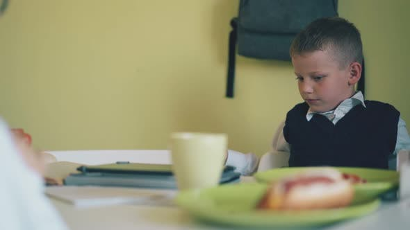 Schoolkid Talks To Friend at Table with Fastfood in Canteen