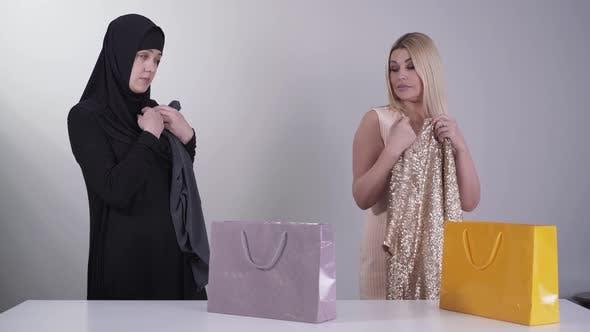 Thumbnail for Portrait of Muslim and Caucasian Women Admiring New Dresses