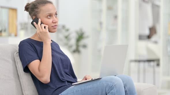 Thumbnail for African Woman with Laptop Talking on Smartphone at Home