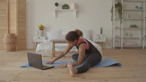 Woman Exercising Watching Fitness Video on Laptop
