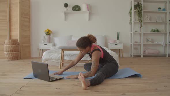 Thumbnail for Woman Exercising Watching Fitness Video on Laptop