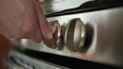 The Hand Turns on the Gas Stove in the Kitchen