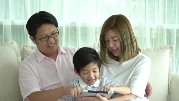 Asian Family Using Tablet At Home